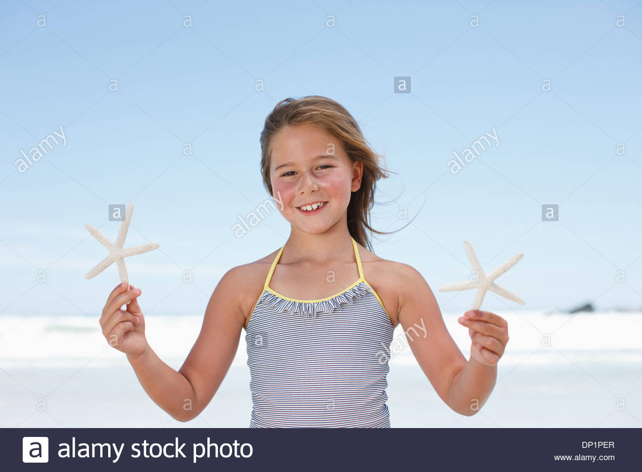 Ragazza con stella di mare sulla spiaggia Immagini Stock