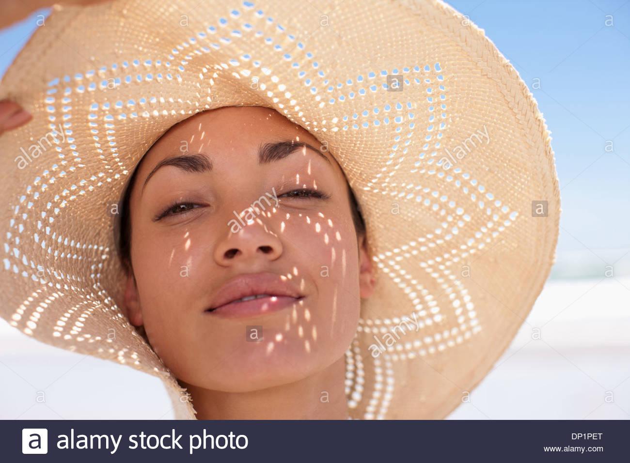 Donna che indossa cappello per il sole sulla spiaggia Immagini Stock