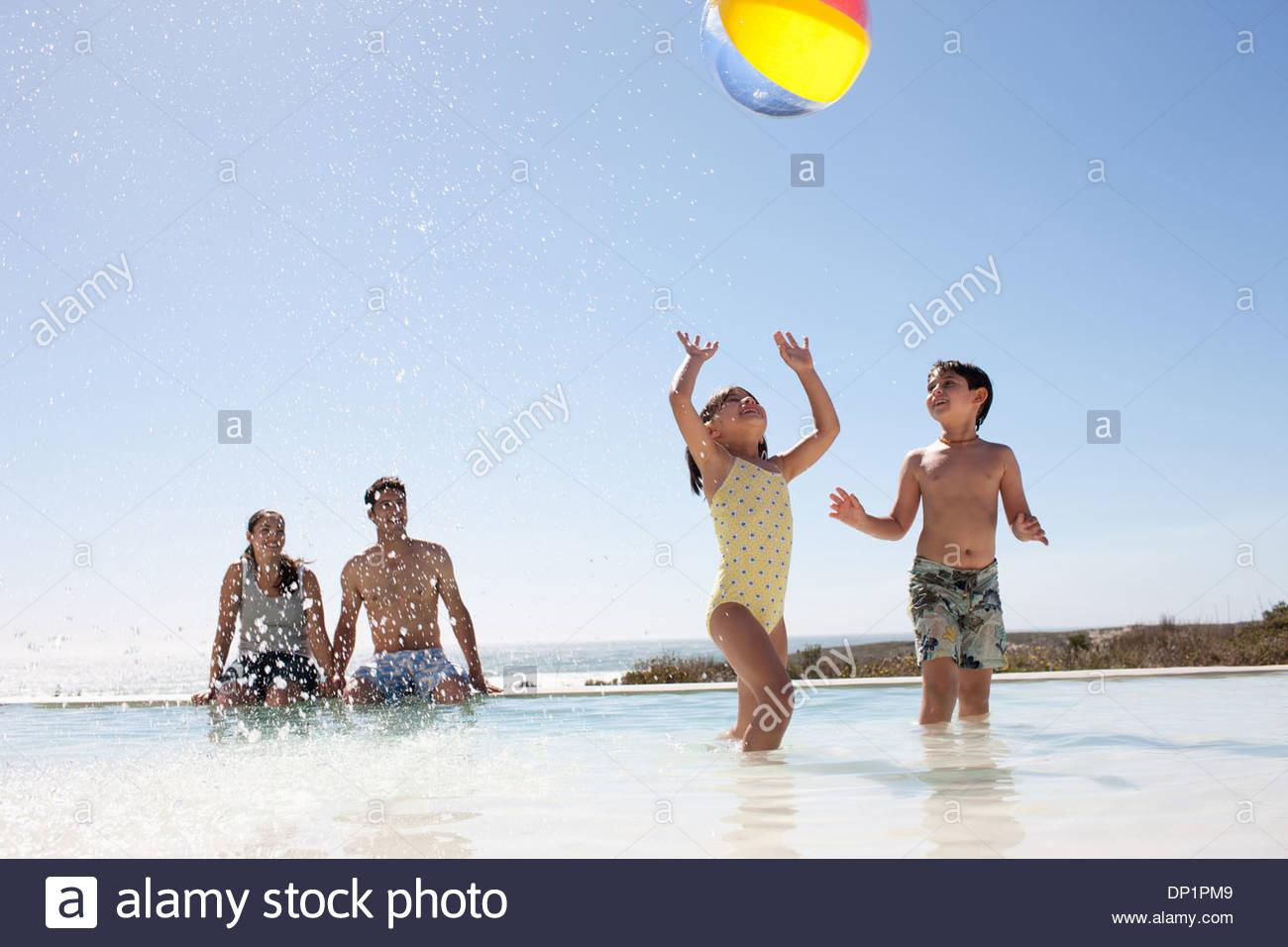 La famiglia gioca con la palla in piscina Immagini Stock