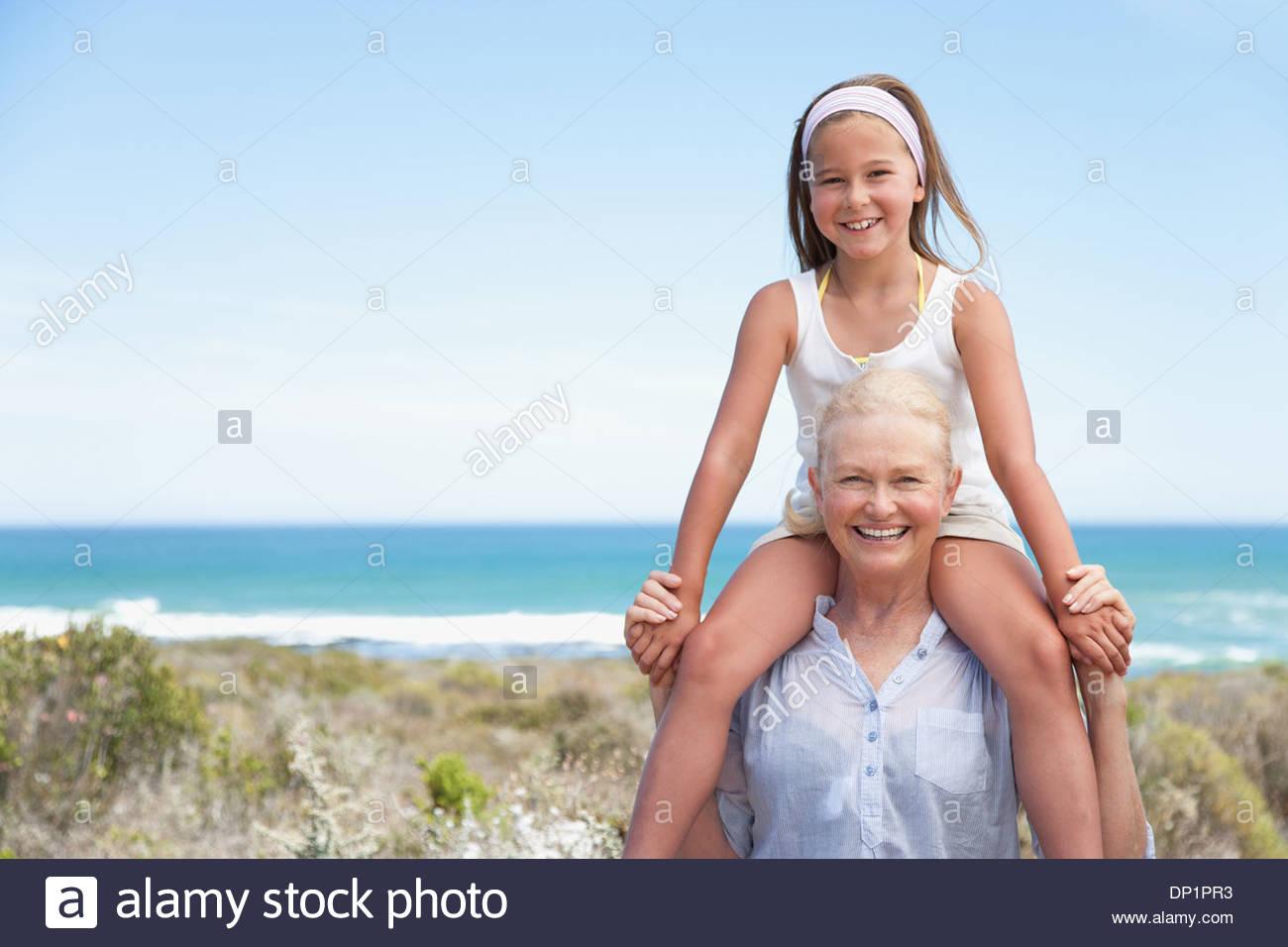 Nonna nipote che porta sulle spalle sulla spiaggia Immagini Stock