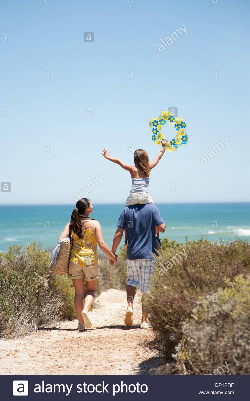 Famiglia passeggiate sulla spiaggia percorso verso l'oceano Immagini Stock