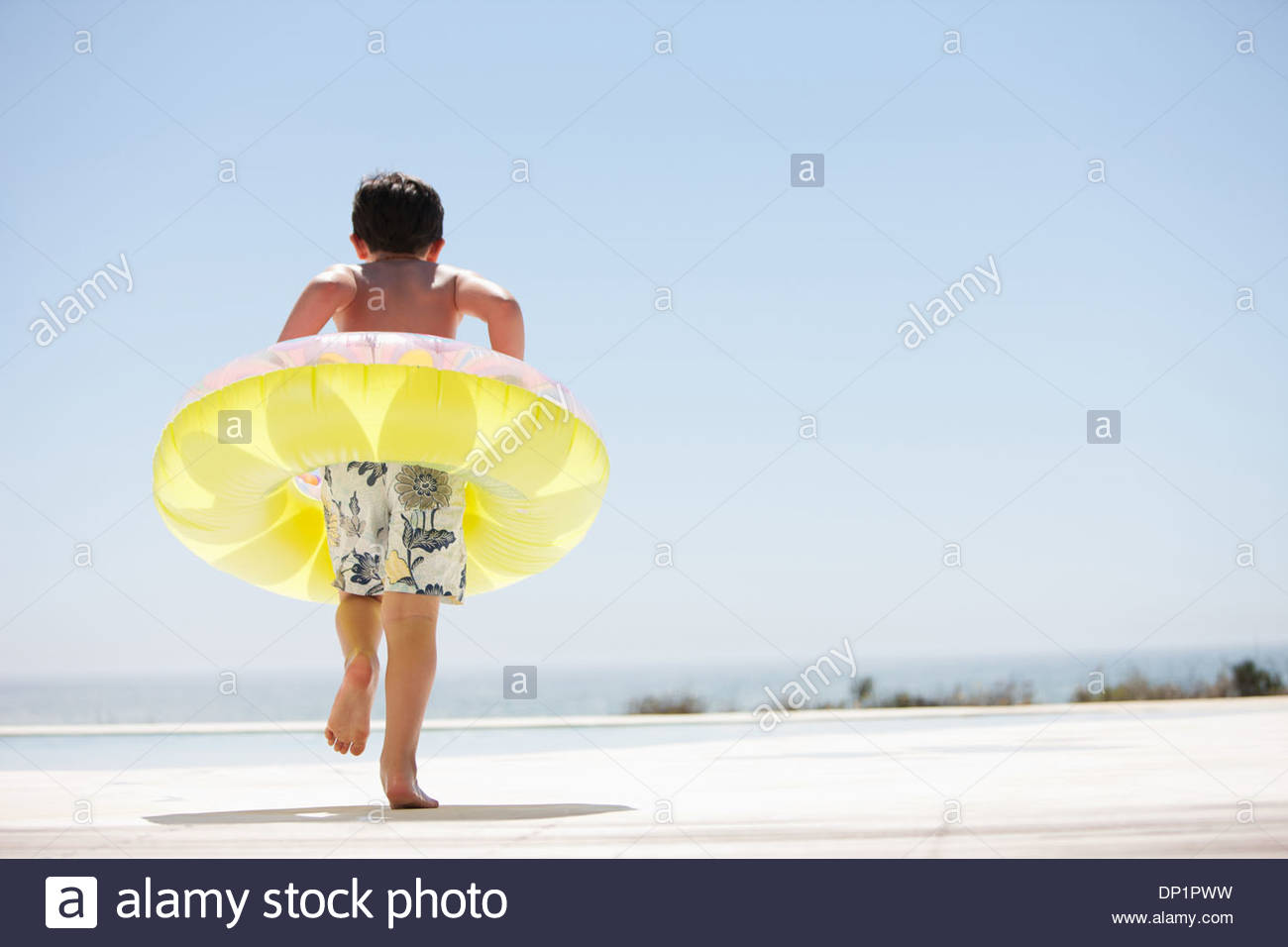 Ragazzo con anello gonfiabile uscendo di piscina infinity Immagini Stock