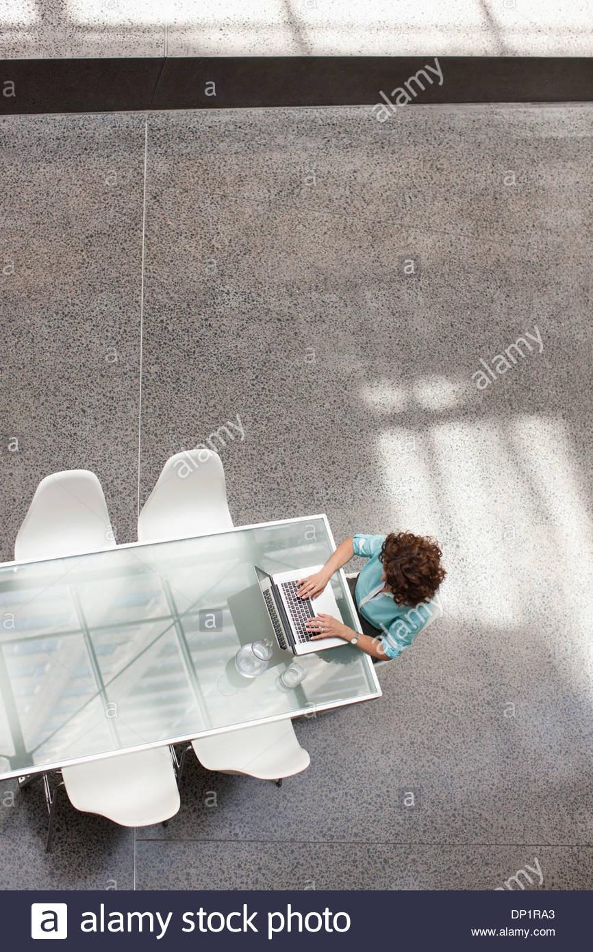 Imprenditrice utilizzando il portatile in un tavolo per conferenza Immagini Stock