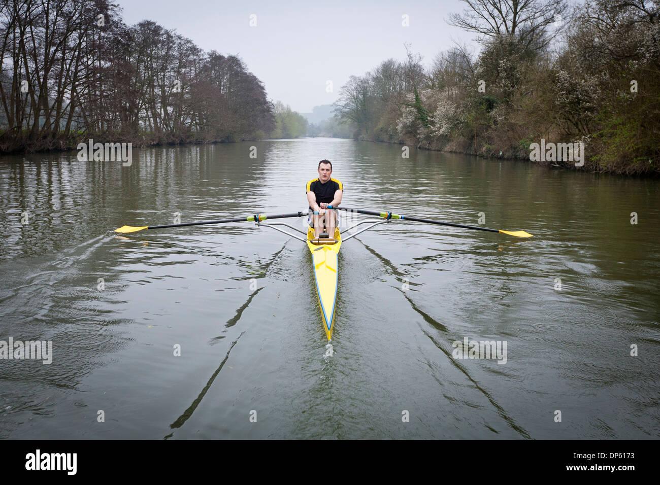 Un uomo in un singolo scull barca a remi sul fiume Avon a Bath, Regno Unito. Immagini Stock