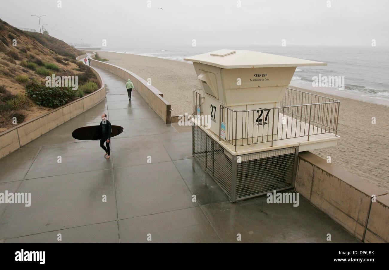 Oct 16, 2006; Carlsbad, CA, Stati Uniti d'America; Drizzly tempo grigio copre la costa come Carlsbad surfer KEITH SCHILLER passeggiate attraverso il Carlsbad Sea Wall dopo l'uscita dell'acqua e il surf onde piccole. Credito: Foto di Charlie Neuman/SDU-T/ZUMA premere. (©) Copyright 2006 by SDU-T Foto Stock
