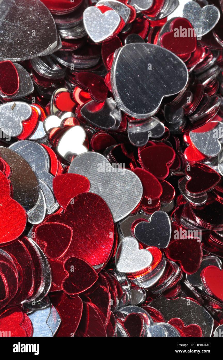 Rosso e argento a forma di cuore i coriandoli a dispersione Immagini Stock