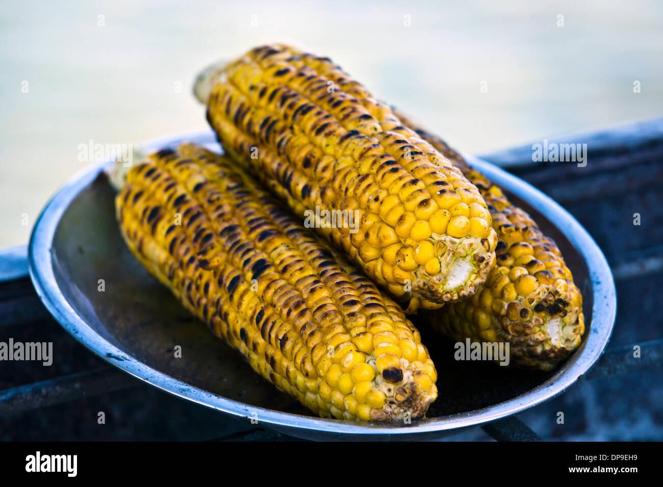 Arrosto di trio di sulla pannocchia di mais. Immagini Stock