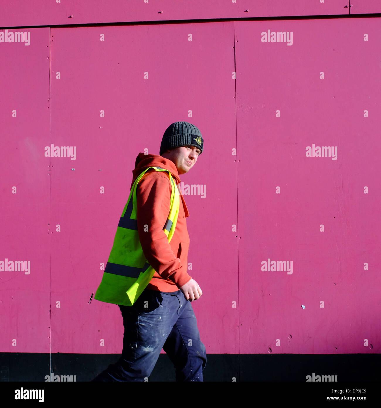 Uomo che indossa alta visibilità giacca passeggiate passato sito rosa imbarco Immagini Stock