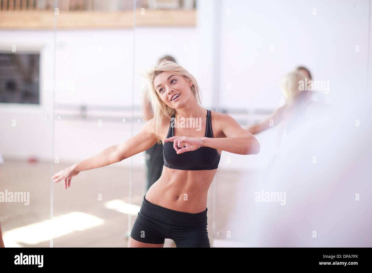 Giovane donna stiramento nella classe di aerobica Immagini Stock