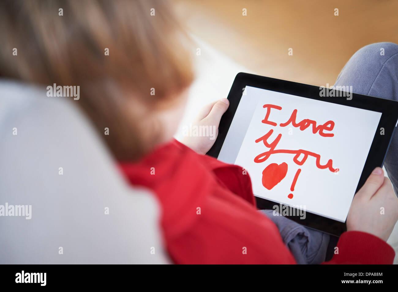 """Vista posteriore del boy holding tablet dicendo """"ti amo"""" Immagini Stock"""