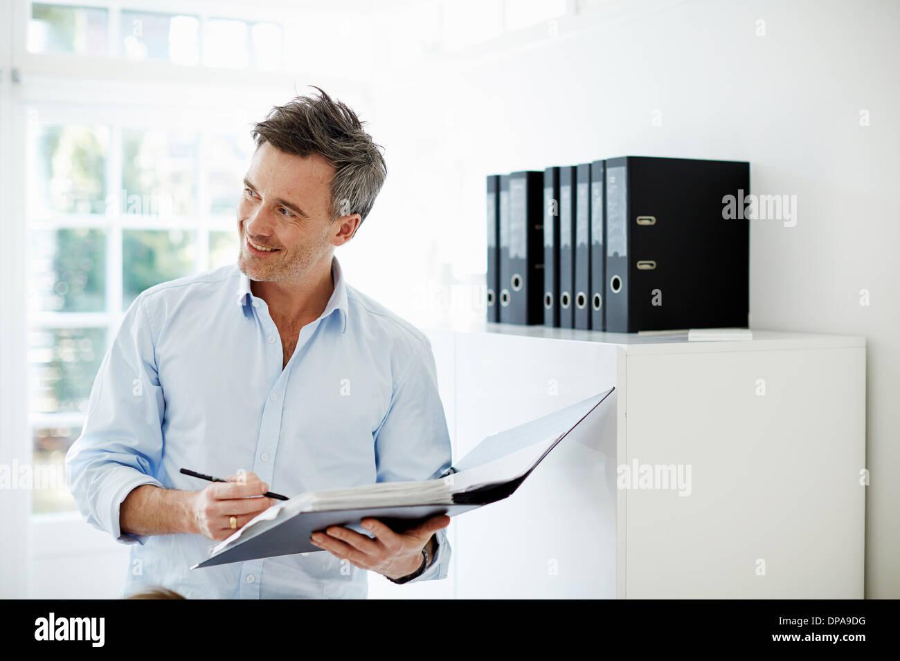 Uomo che guarda a una cartella di documenti Immagini Stock