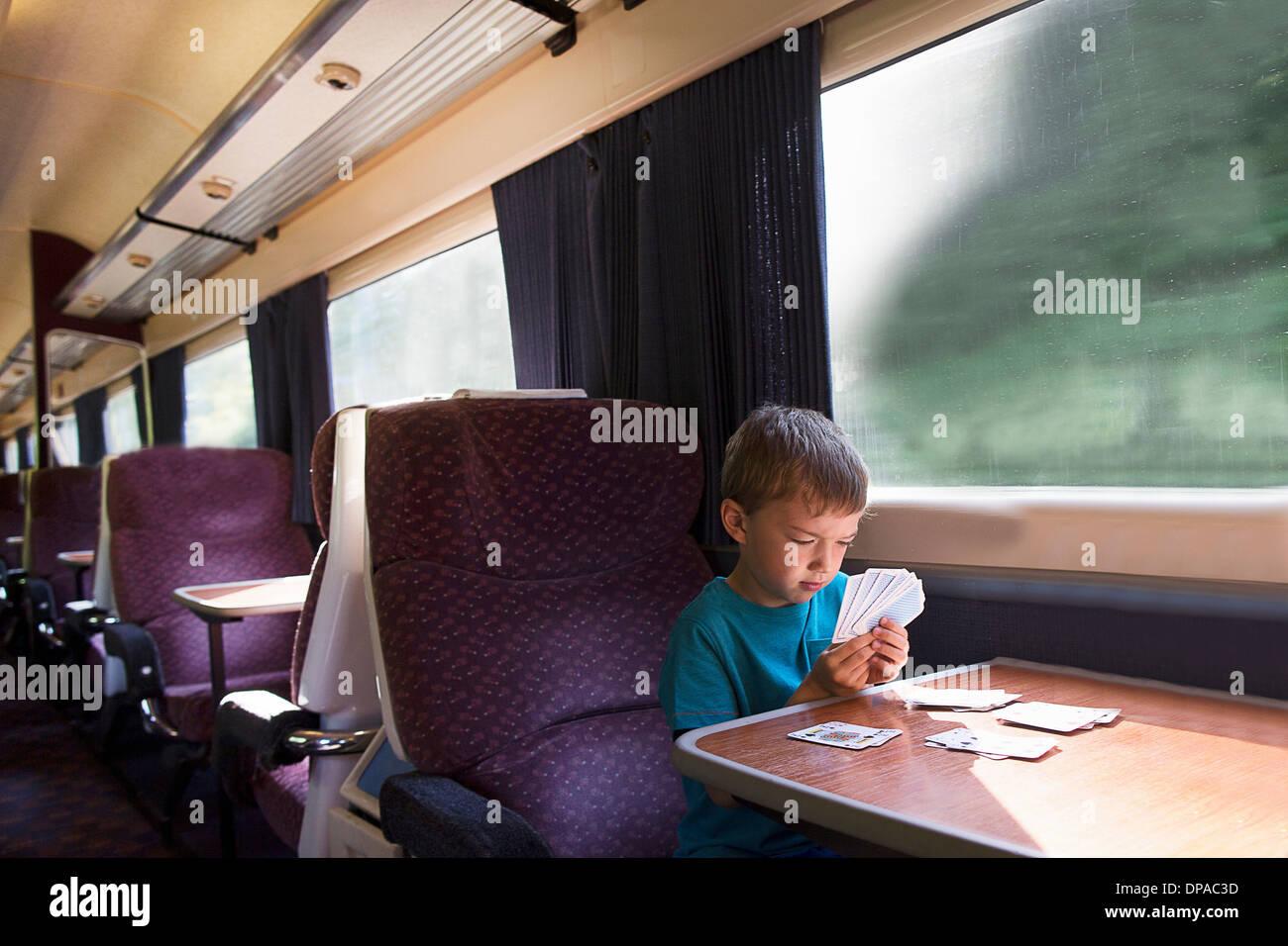 Giovane ragazzo giocando pazienza sul treno Immagini Stock