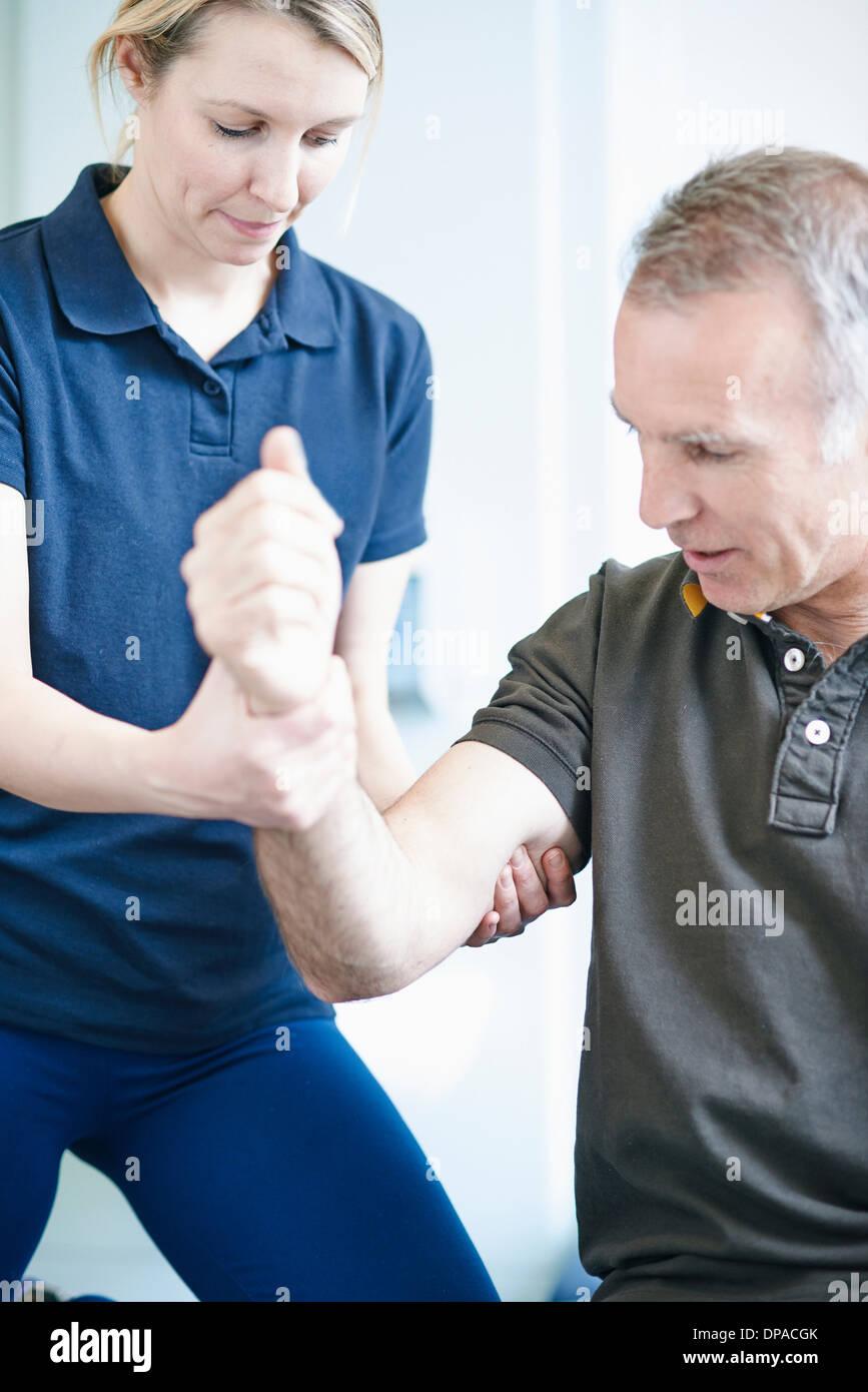 Fisioterapista aiutare l uomo a fare esercizio del braccio Immagini Stock