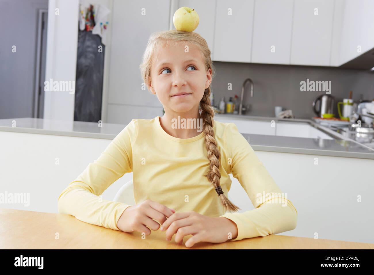 Ragazza con apple bilanciato sulla sua testa Immagini Stock