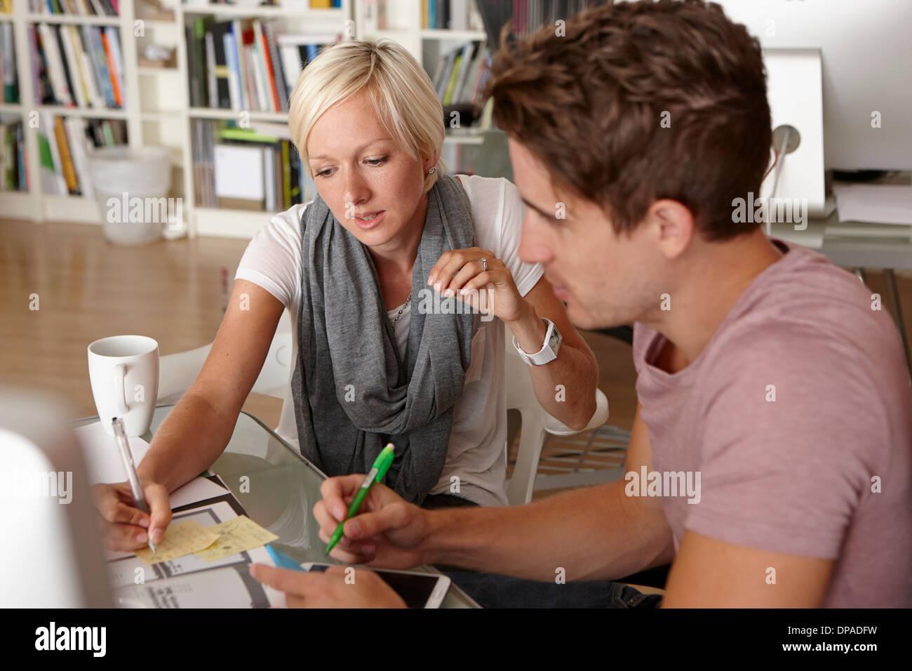 Due colleghi parlare, donna rendendo note Immagini Stock