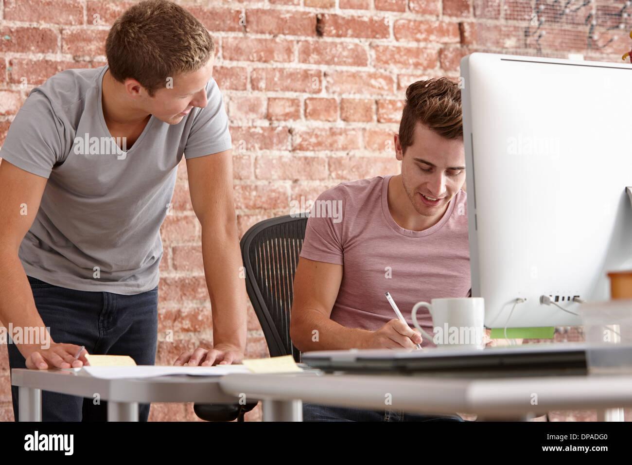 I giovani uomini a parlare alla scrivania con computer Immagini Stock