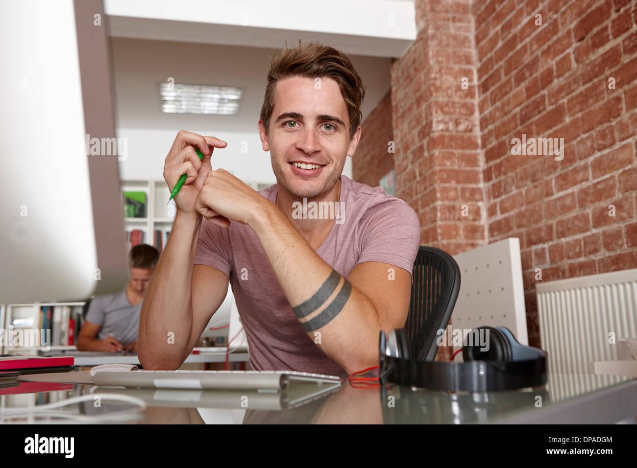 Ritratto di giovane uomo alla scrivania Immagini Stock