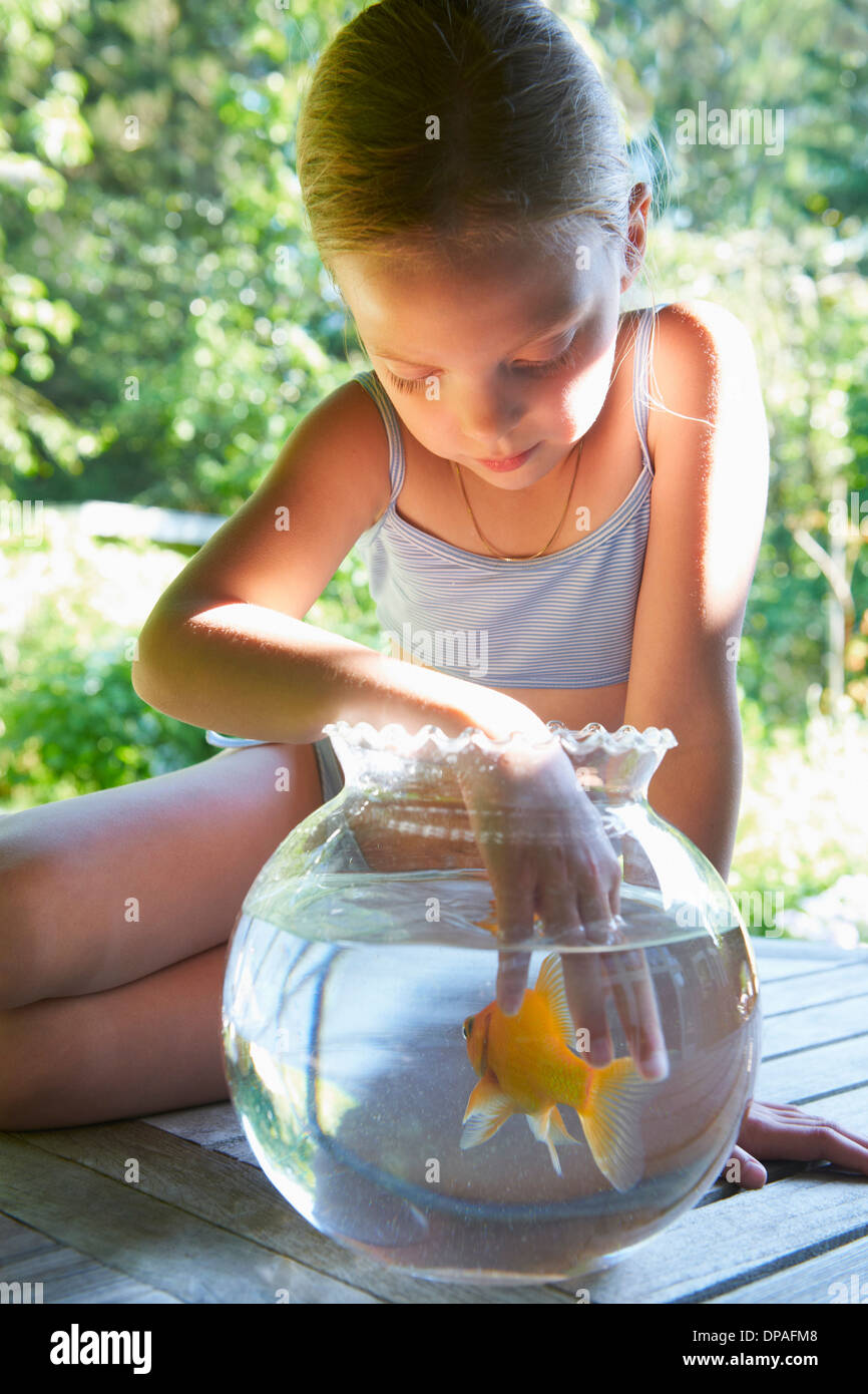 Ragazza giovane con le dita in Goldfish Bowl Immagini Stock