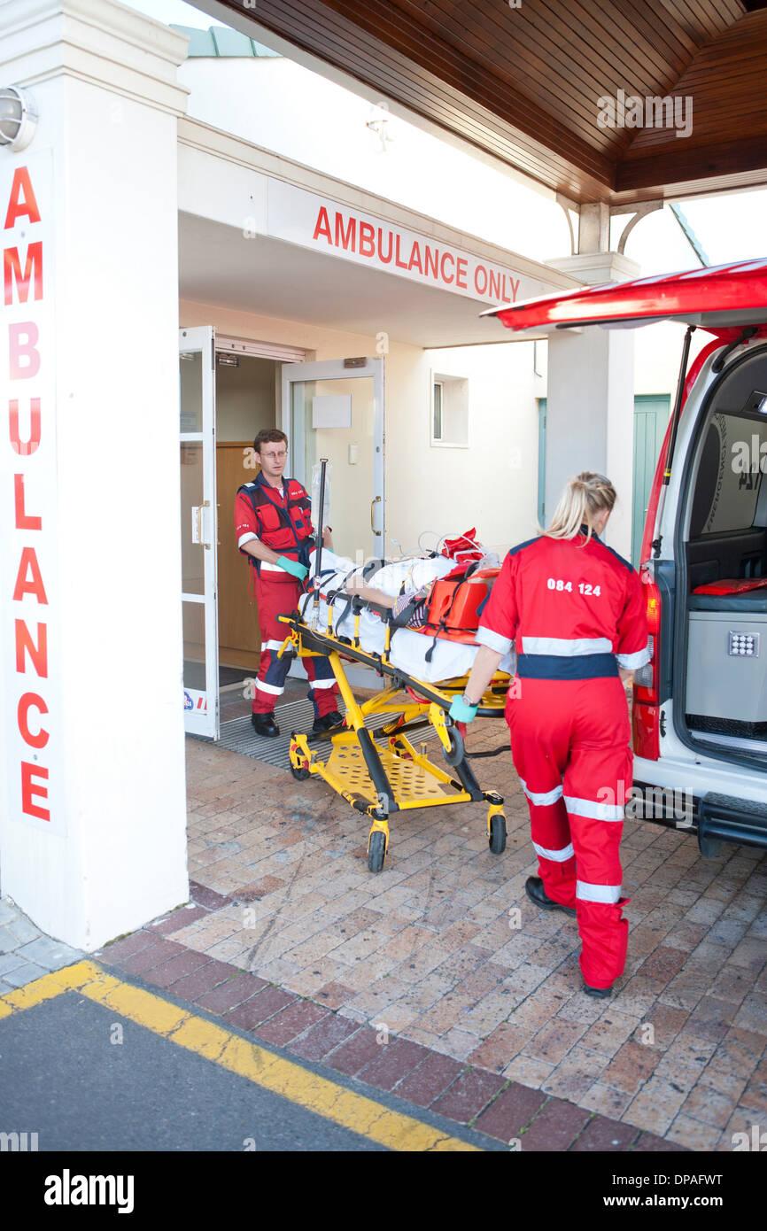 I paramedici spostamento del paziente attraverso la porta dell'ospedale Immagini Stock