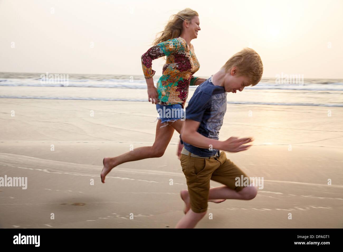 Madre e figlio in esecuzione sulla spiaggia Immagini Stock