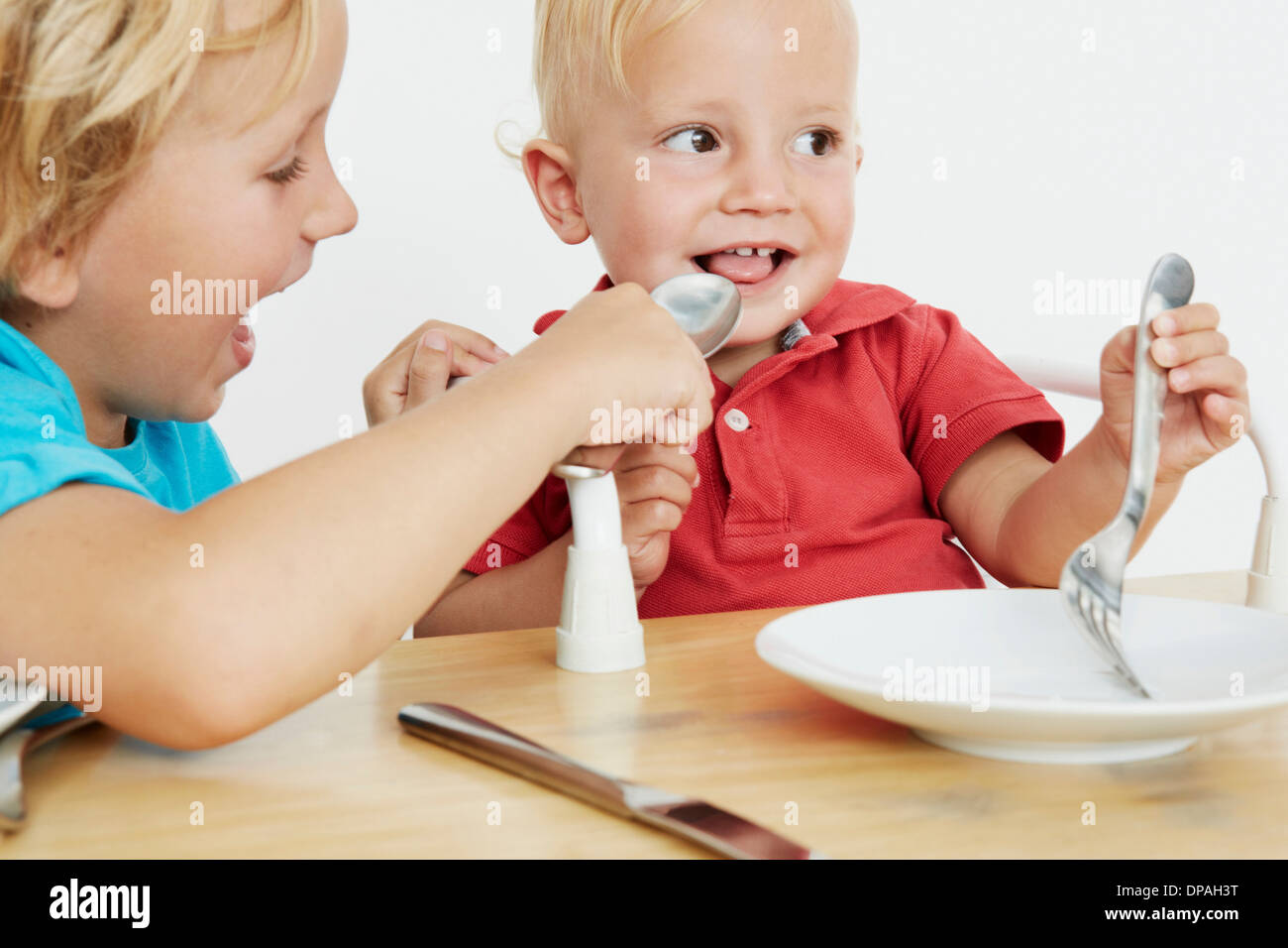 Due giovani ragazzi a tavola, una finta di alimentare le altre Foto Stock