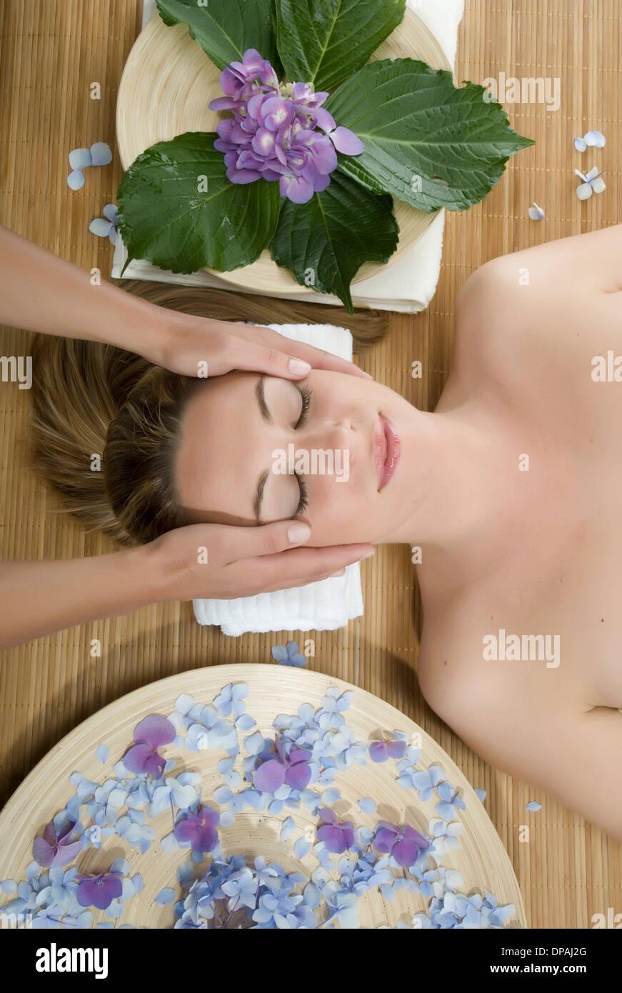 Donna sdraiata con massaggio della testa Foto Stock