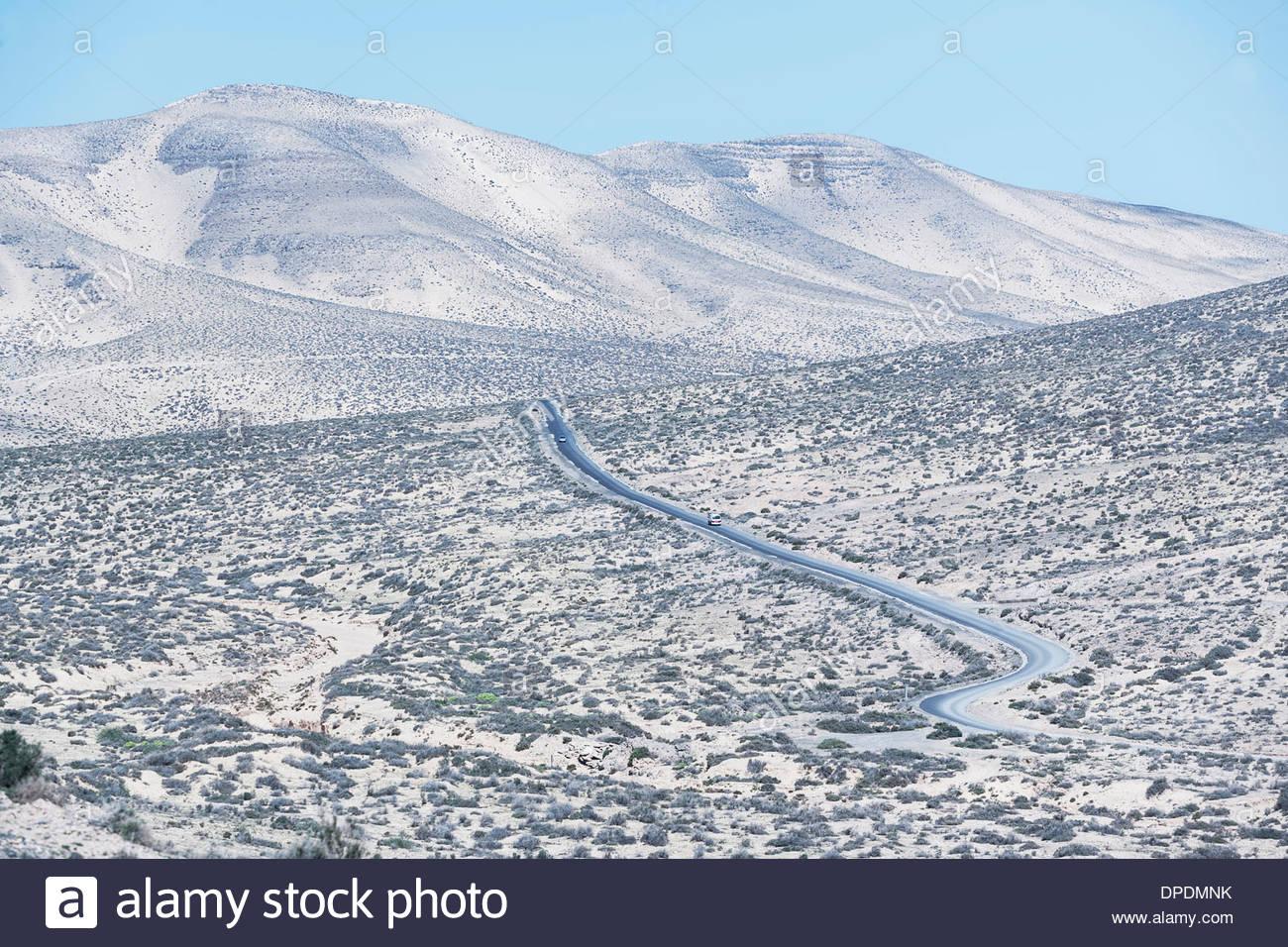 Avvolgimento su strada attraverso il paesaggio di Fuerteventura, Isole Canarie, Spagna Immagini Stock