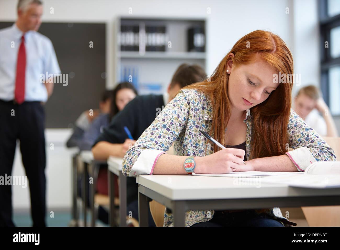 Insegnante a guardare oltre gli adolescenti in aula Immagini Stock