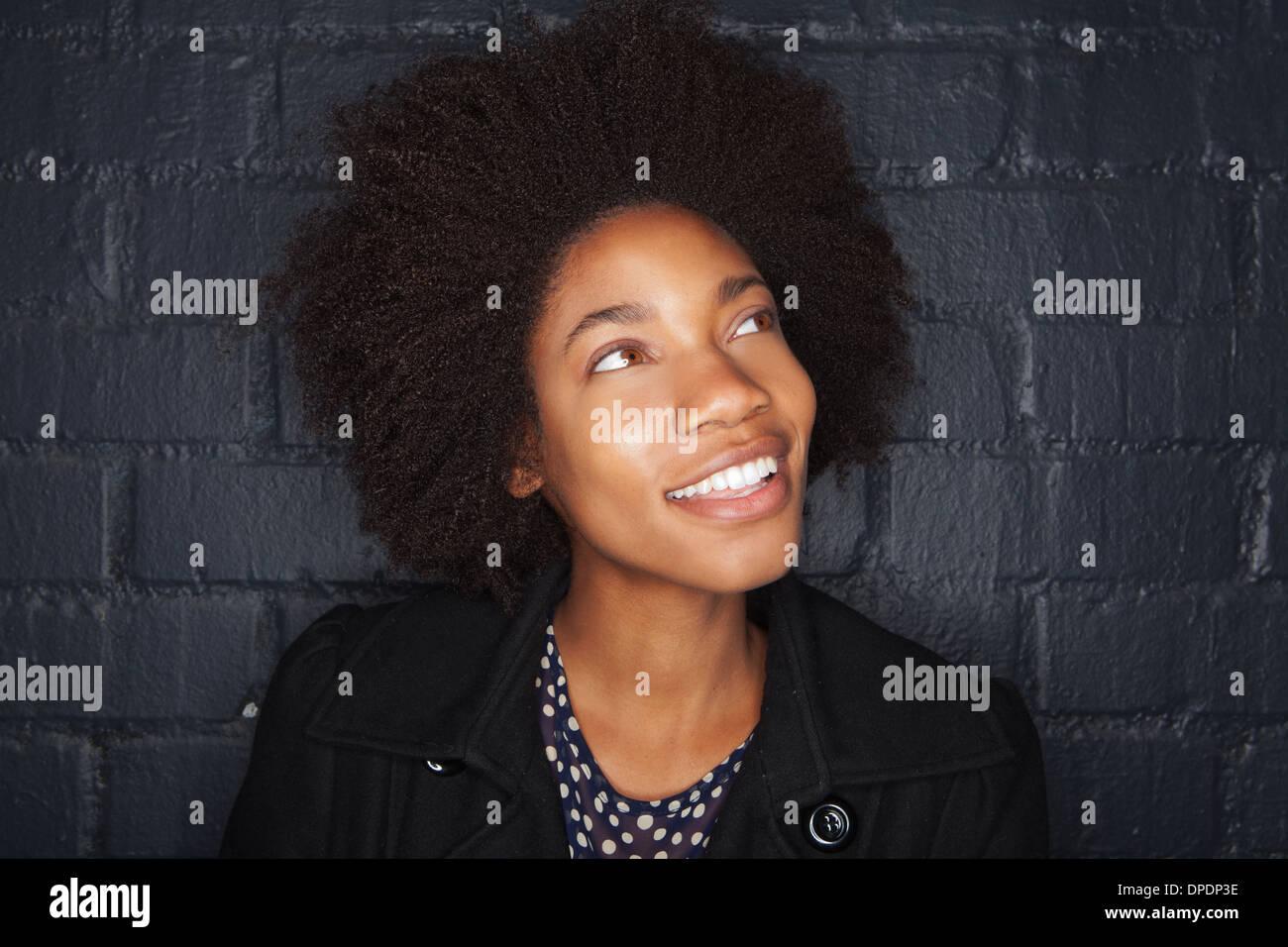 Giovane donna da nero a un muro di mattoni che guarda lontano Immagini Stock