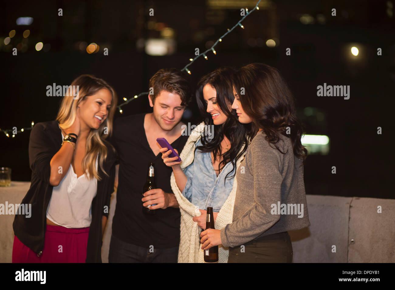 Giovani amici adulti guardando il telefono cellulare al partito sul tetto Immagini Stock