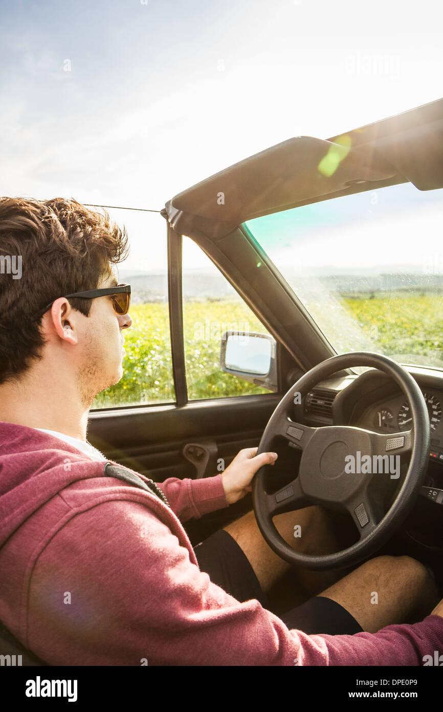 Giovane uomo pendente convertibile di guida Immagini Stock