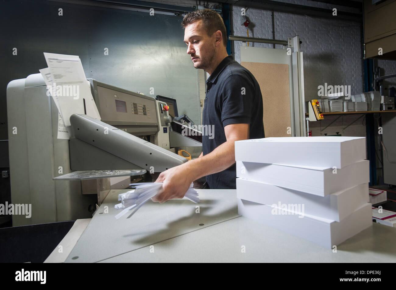 Lavoratore di smaltimento di carta inceppata nel laboratorio di stampa Immagini Stock