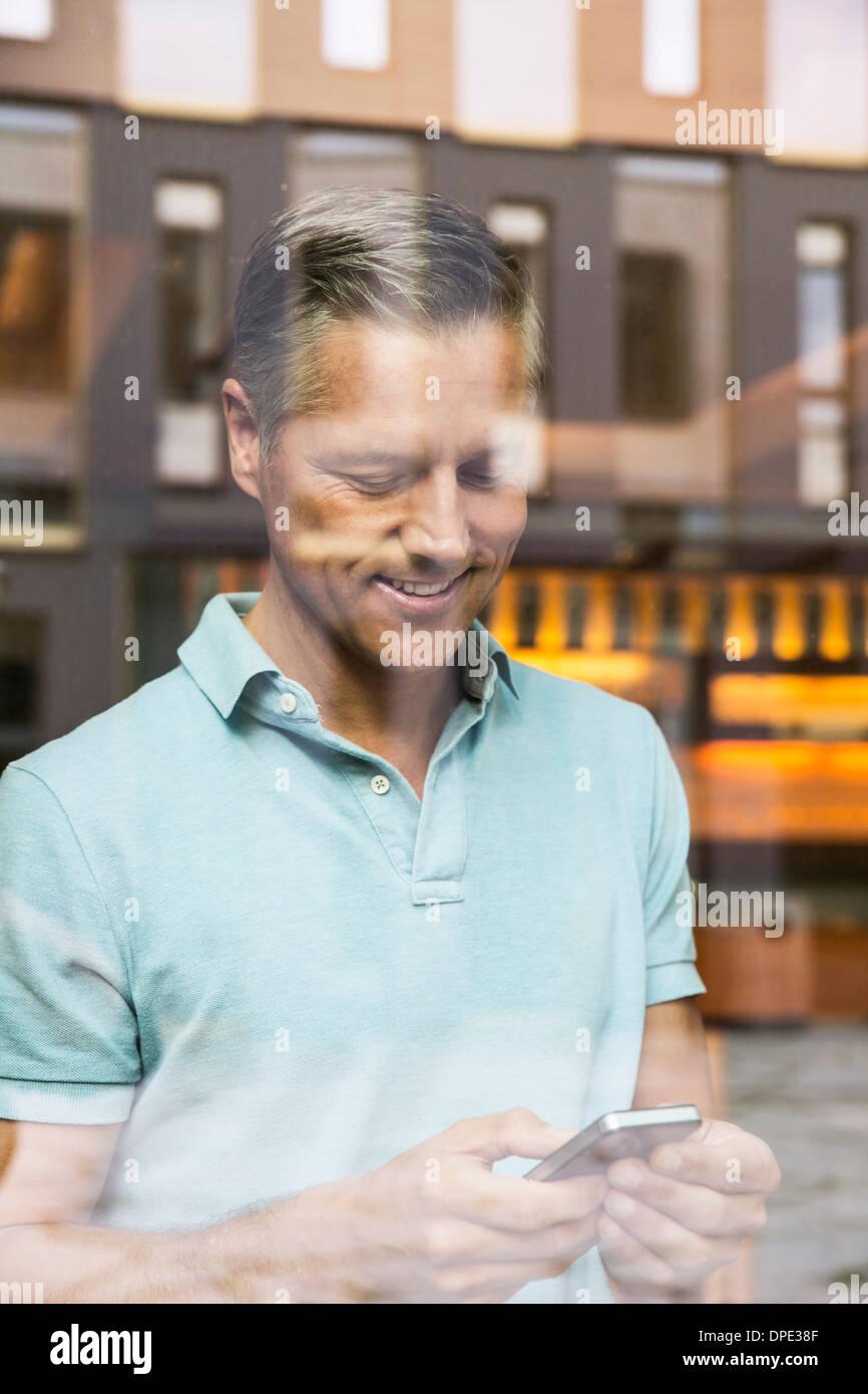 Imprenditori facendo chiamata telefonica, vista attraverso la finestra Immagini Stock