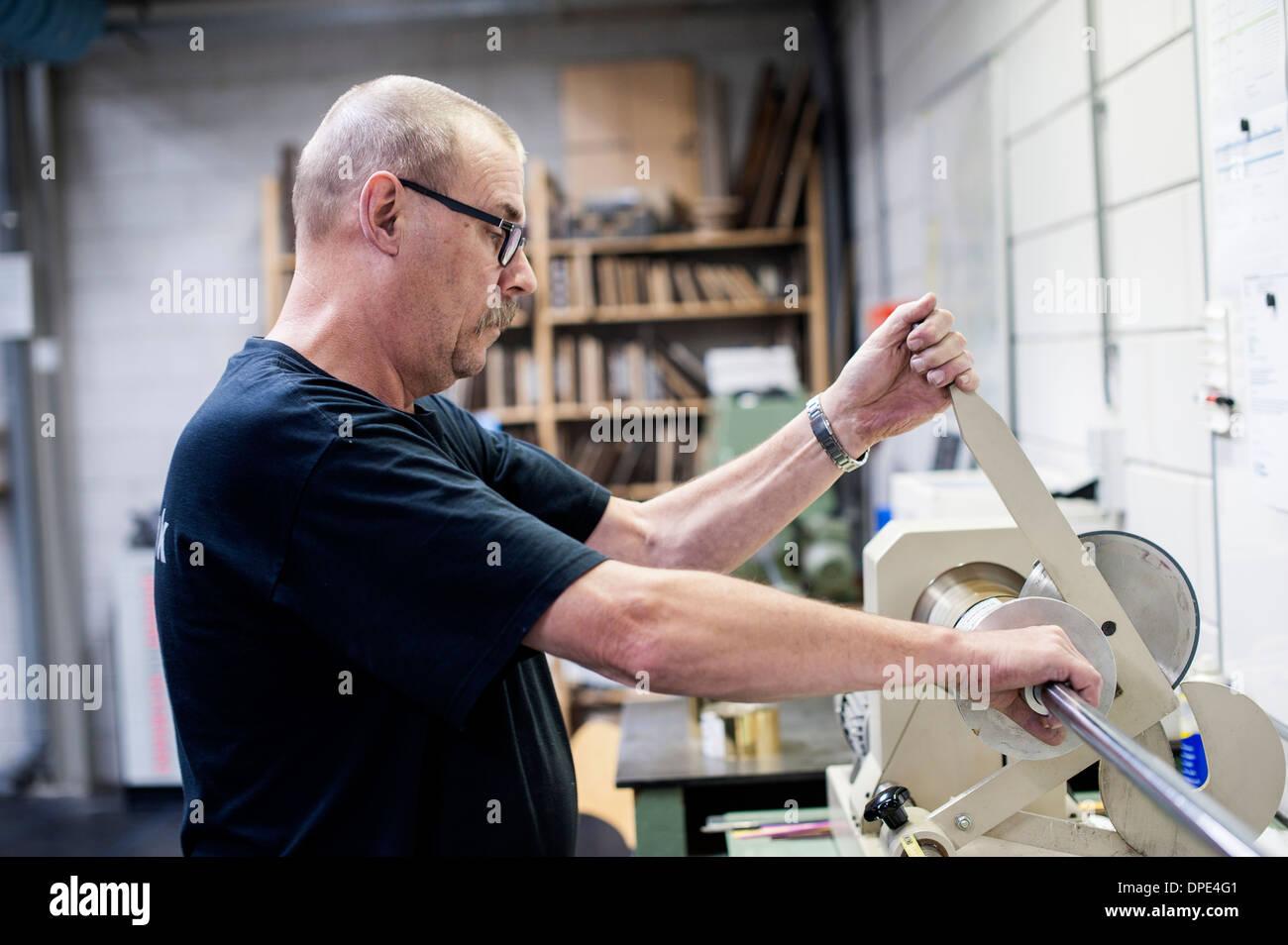 Lavoratore di funzionamento della macchina di taglio in carta stampa workshop Immagini Stock