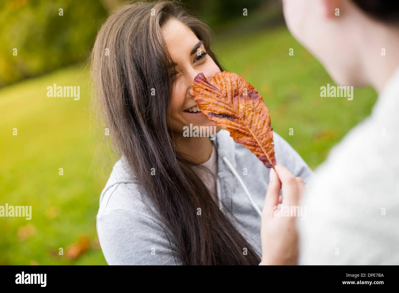 Giovane donna foglia di contenimento Foto Stock