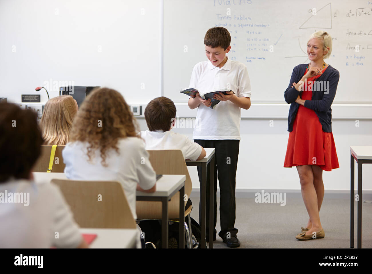 Scolaro di lettura dal libro di testo nella parte anteriore della classe Foto Stock