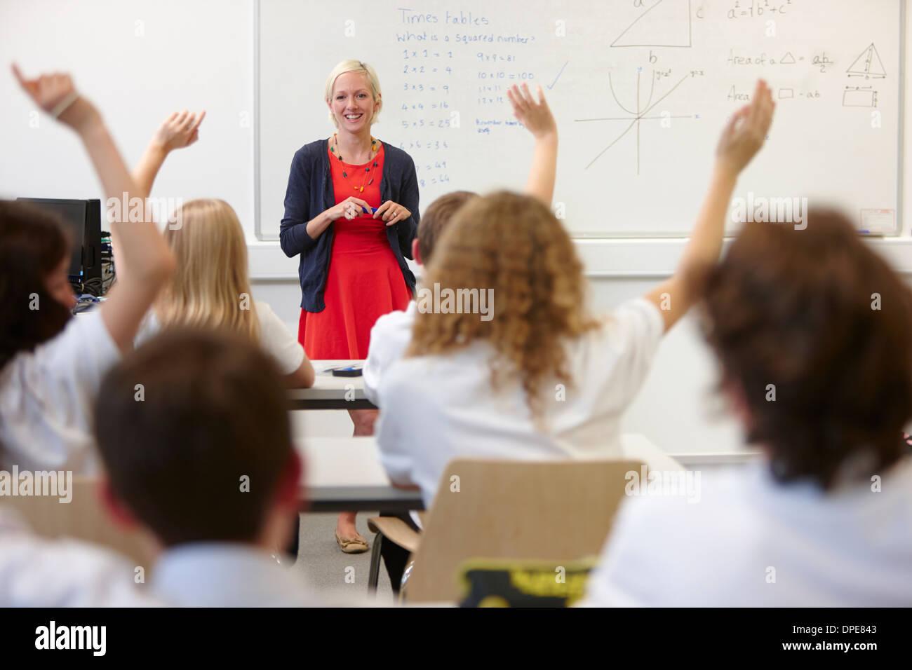 Femmina e insegnante di classe con le mani alzate Immagini Stock