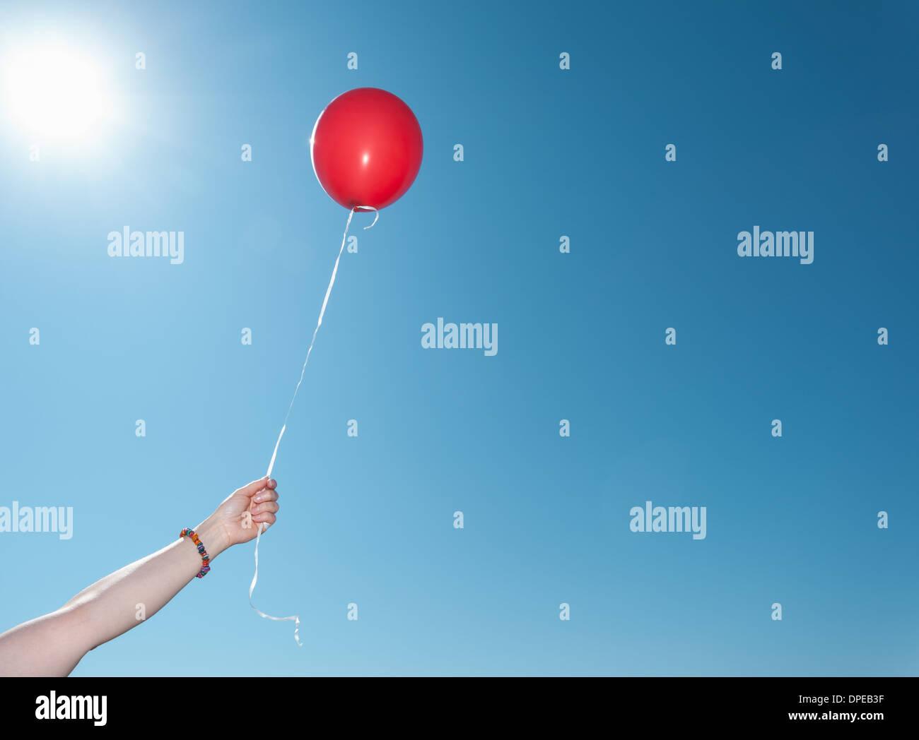 Mano azienda singolo palloncino rosso contro il cielo blu Immagini Stock