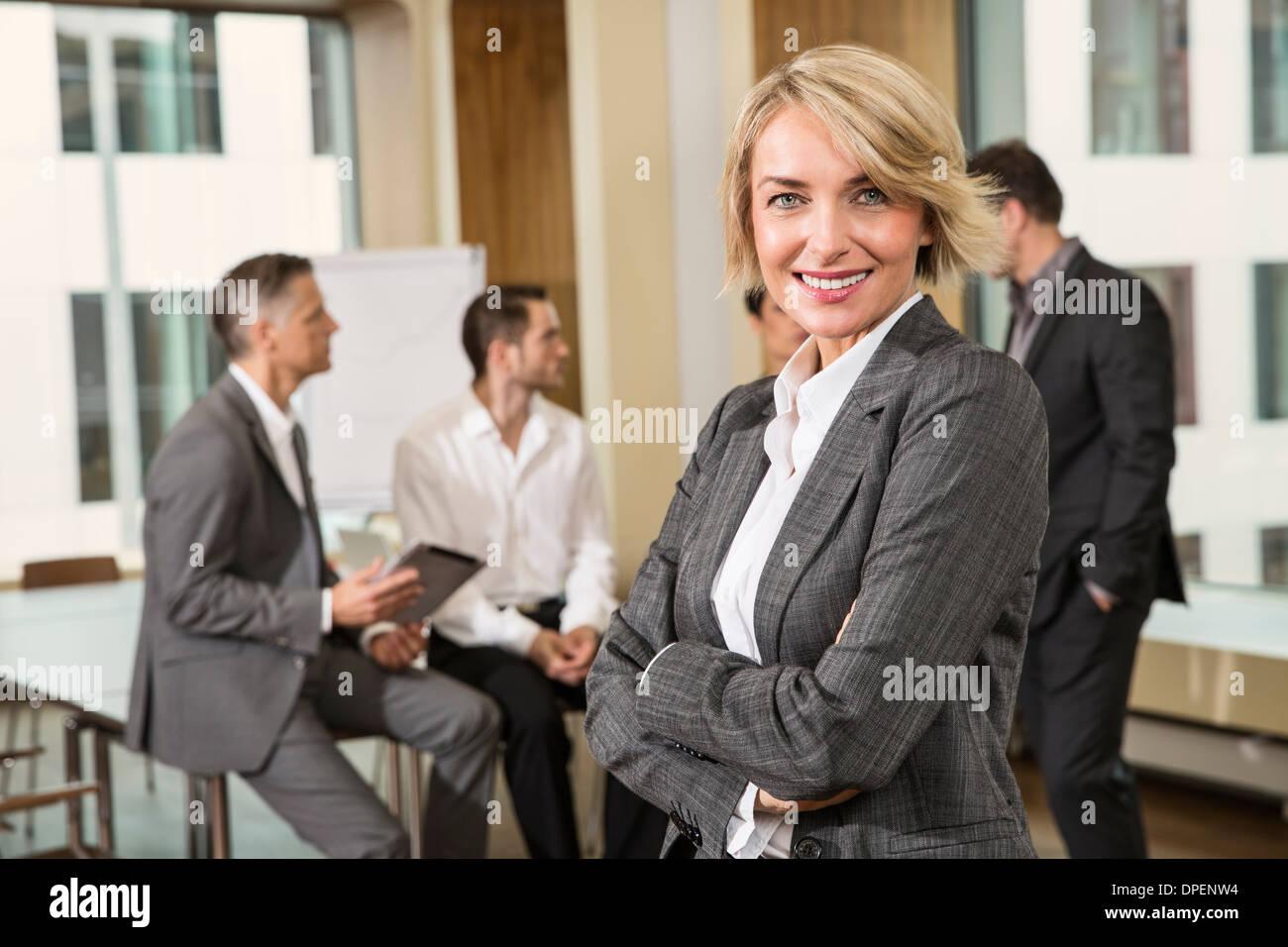 Imprenditrice in piedi di fronte ai colleghi Immagini Stock