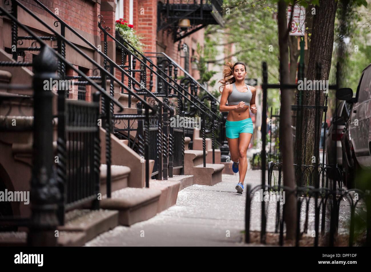 Donna jogging sul marciapiede Immagini Stock
