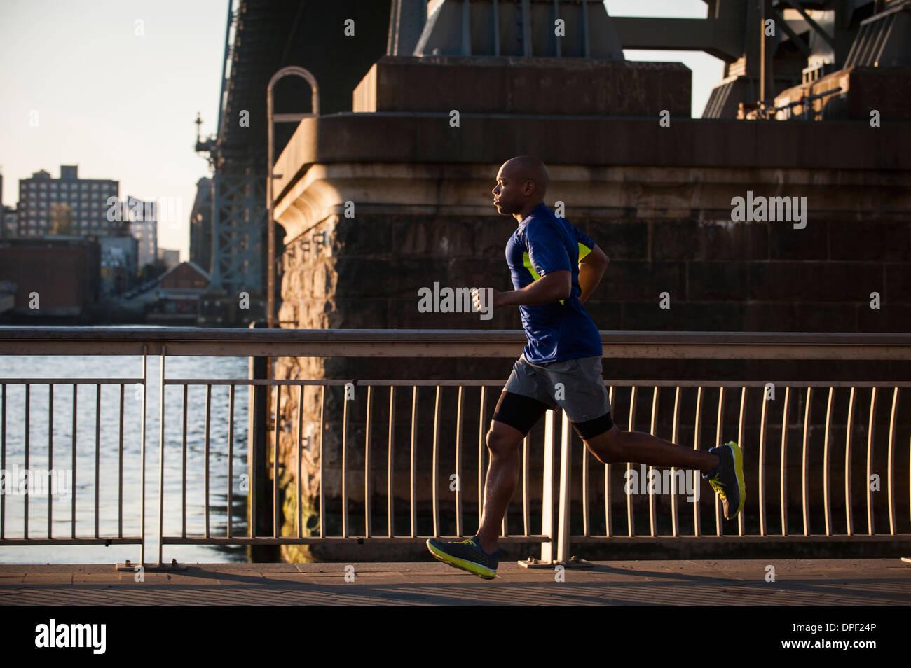 Uomo di jogging sul marciapiede Immagini Stock