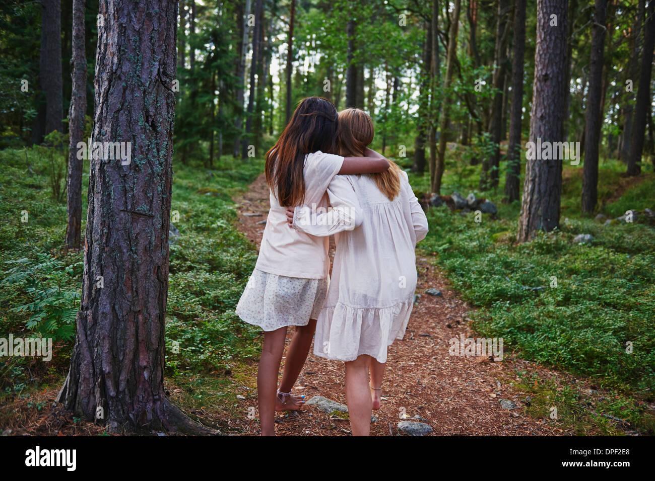 Le ragazze adolescenti con bracci intorno a ogni altra foresta Immagini Stock