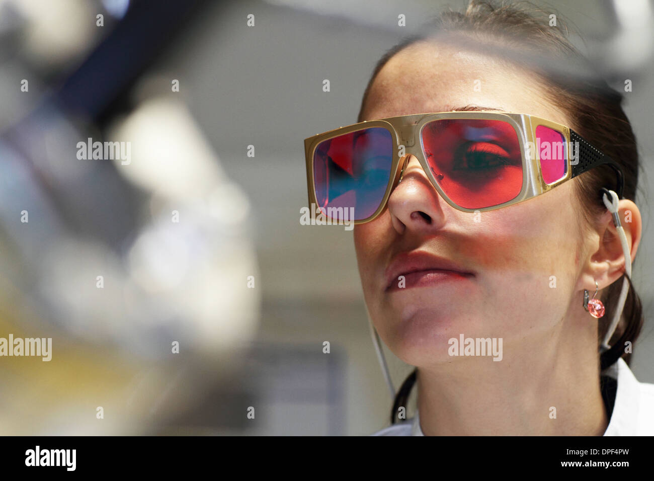 Close up della donna scienziato rosso da indossare gli occhiali di protezione Foto Stock