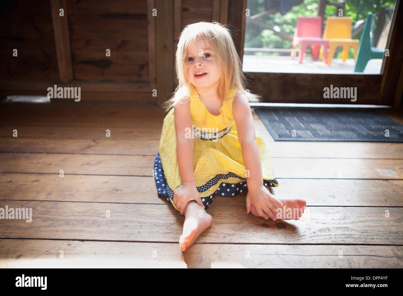 Femmina bambino seduto sul pavimento in legno Immagini Stock