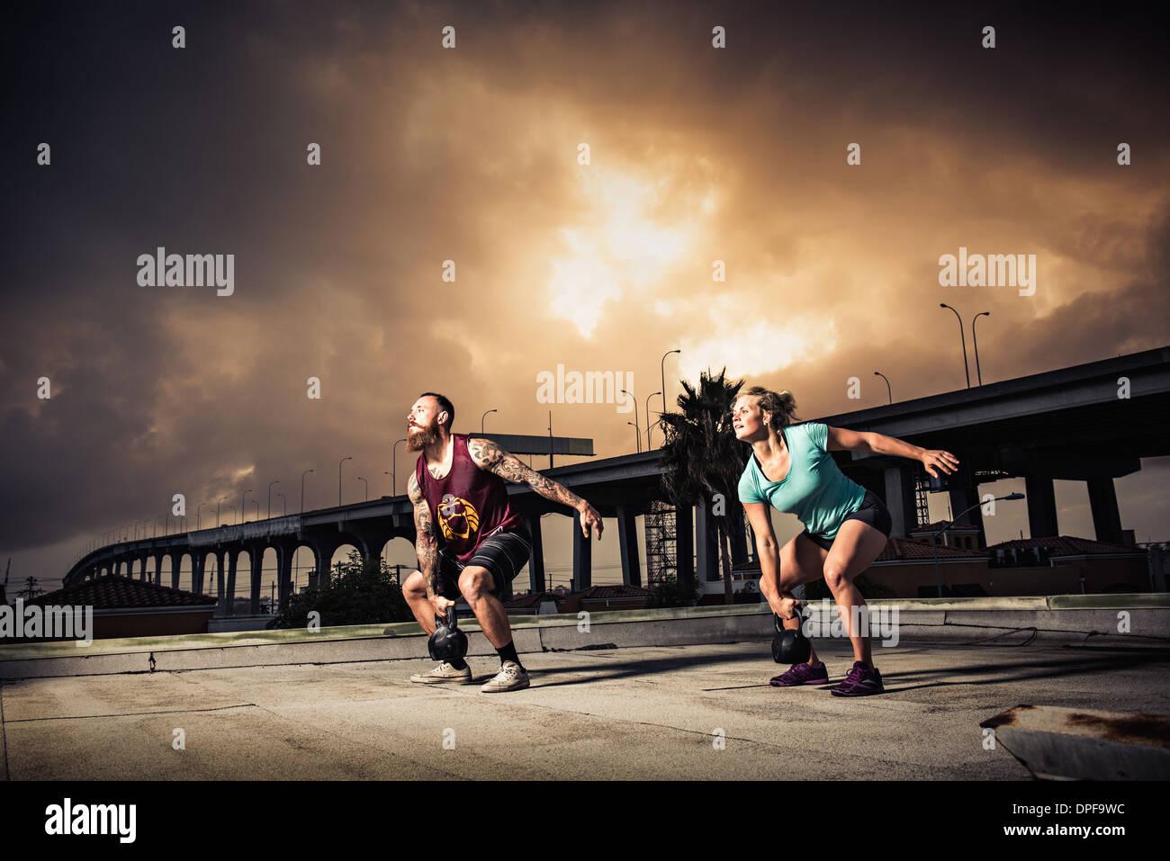 Uomo e donna allenamento con kettlebells palestra sul tetto Immagini Stock