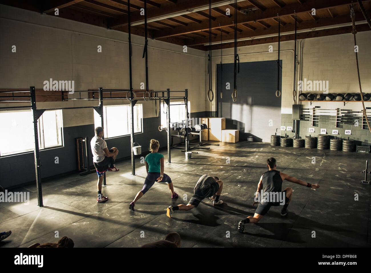 Lezione di fitness in fase di riscaldamento insieme in palestra Immagini Stock