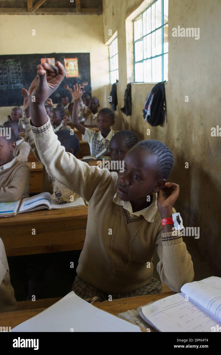 Età primaria ragazza alza la mano per rispondere a una domanda a Rubiri scuola primaria, a Naivasha, Kenya Immagini Stock
