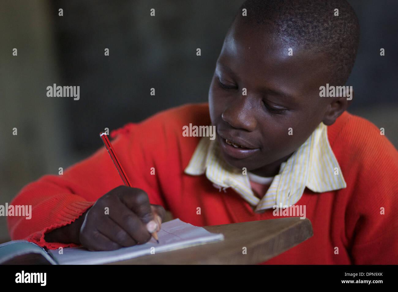 Età primaria boy iscritto nel libro di esercizi a Rubiri scuola primaria a Naivasha, Kenya Immagini Stock