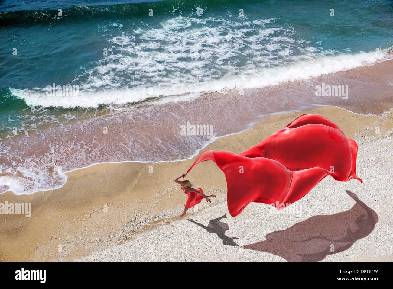 Donna con un tessuto di colore rosso sulla spiaggia Immagini Stock