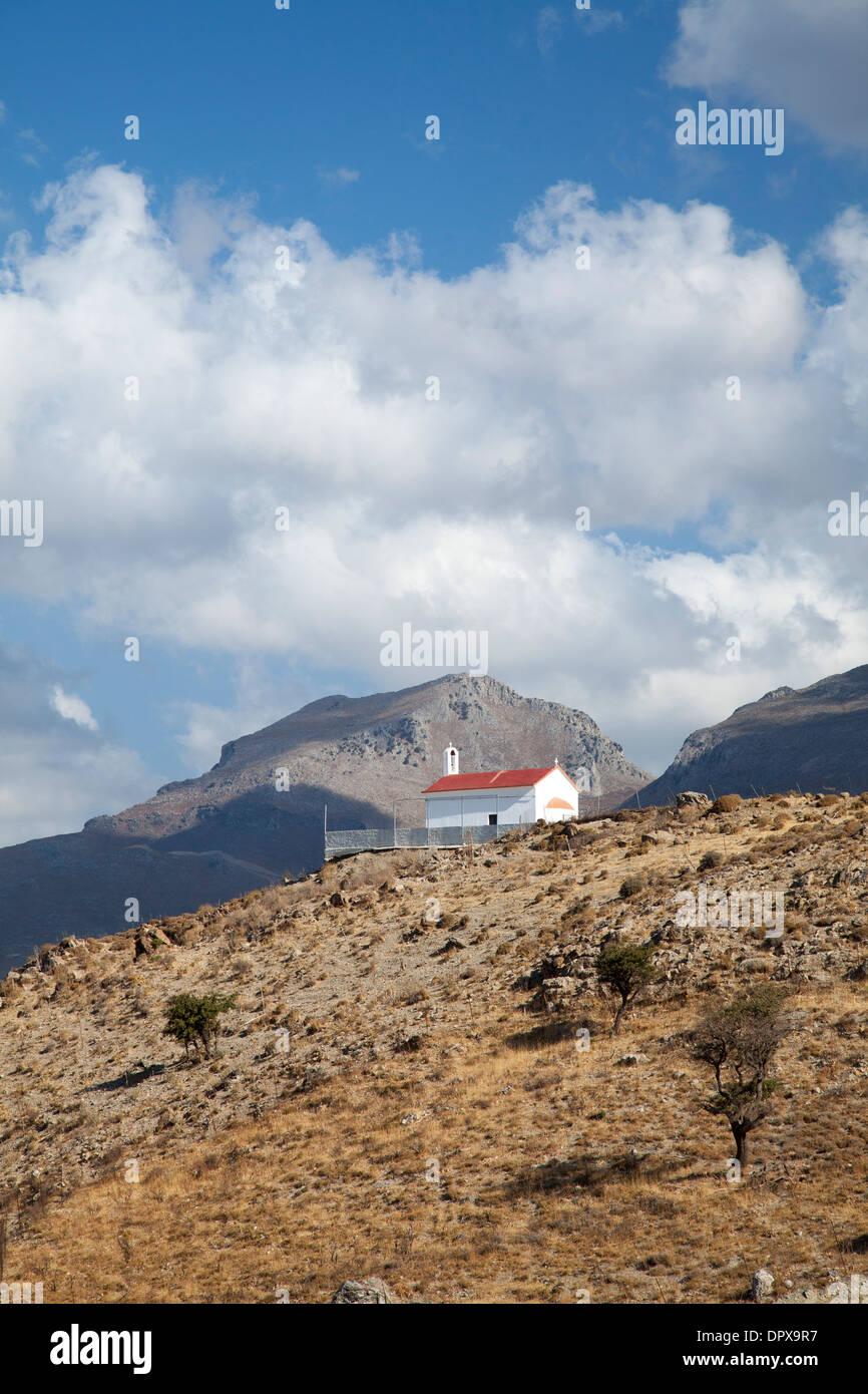 Hill-top chiesa sotto le montagne bianche, vicino a Plakias, Rethymnon distretto, Creta, Grecia. Immagini Stock